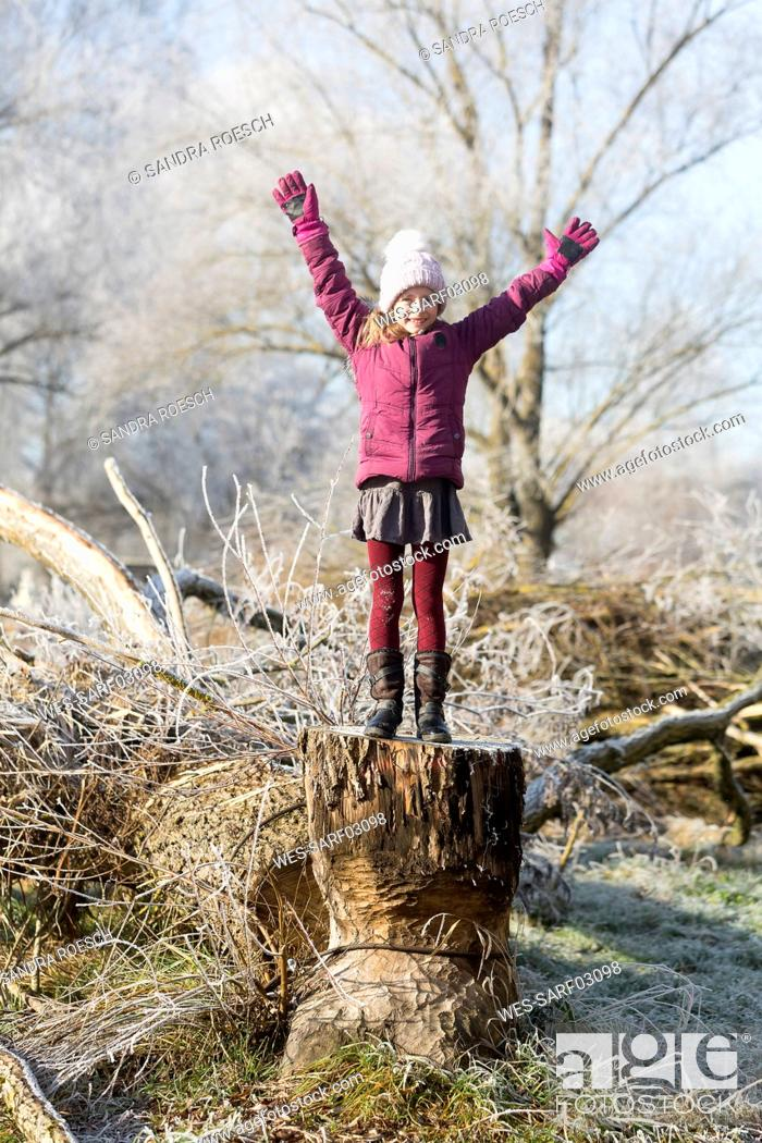 Stock Photo: Portrait of happy girl with arms raised standing on tree trunk in winter.