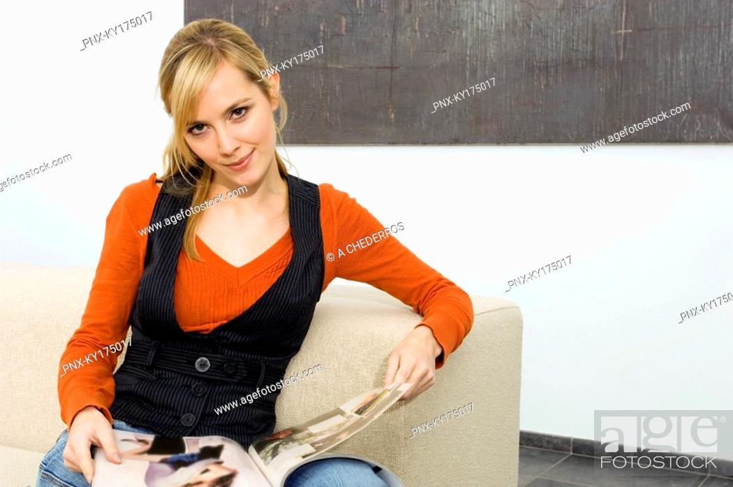 Stock Photo: Portrait of a young woman sitting on a couch and holding a magazine.