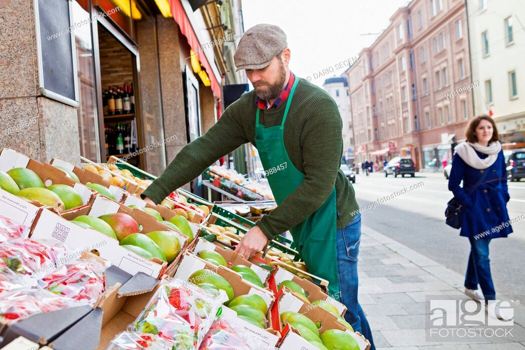 Stock Photo: Greengrocer's shop, grocer arranging crates.