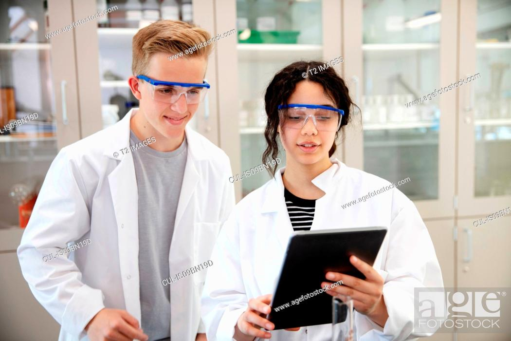 Stock Photo: Students using digital tablet in laboratory.