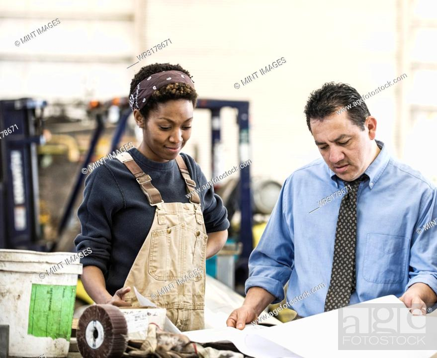 Stock Photo: Hispanic man manager and black woman factory worker going over project plans in a sheet metal factory.