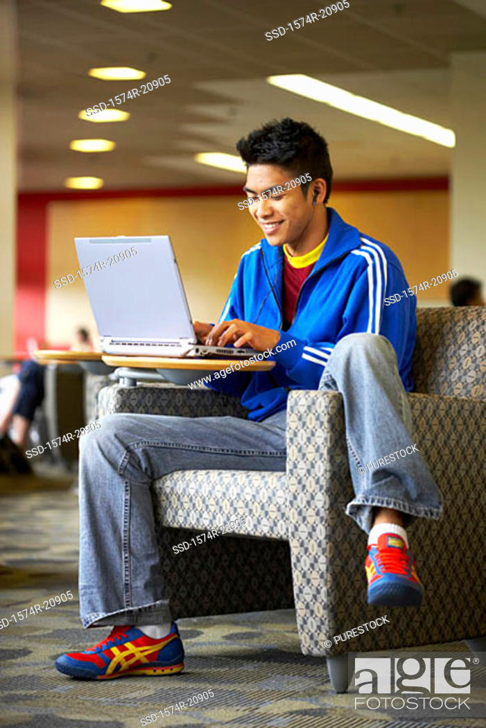 Stock Photo: College student sitting in an armchair and using a laptop.