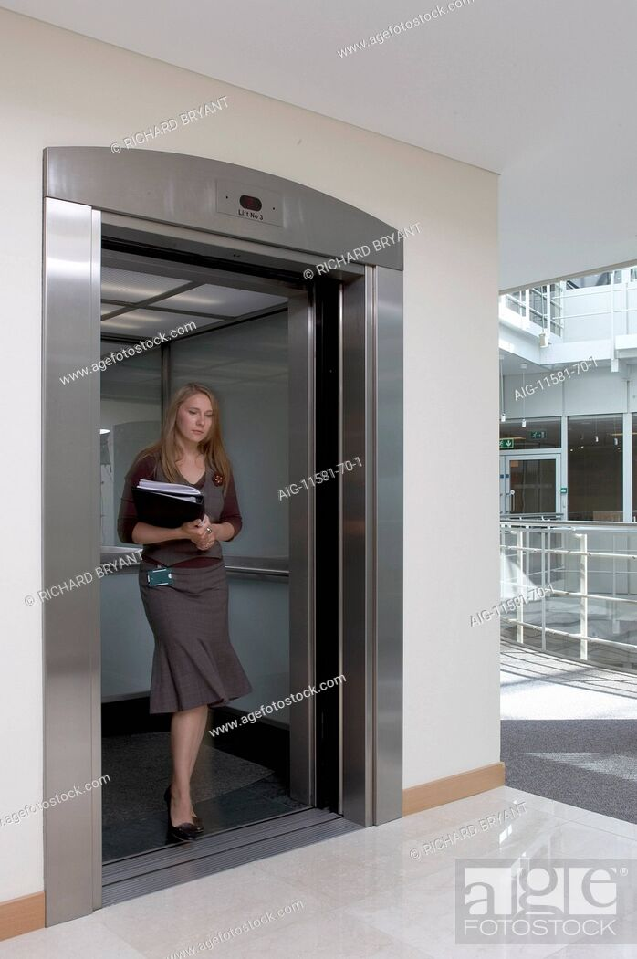 Stock Photo: Office life and interiors part two. Woman stepping out of lift.