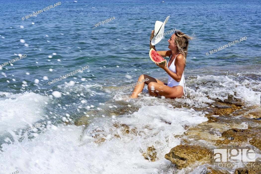 Imagen: woman with water melon and sunhat sitting on rock in sea, water splashes, excitement, holiday, vacation, summer, adventure.