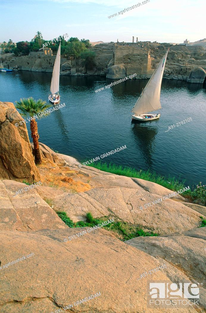 Stock Photo: EGYPT.NUBIA.ASWAN.TWO FELUCCAS ON THE NILE.RED ROCKS AT FORE.
