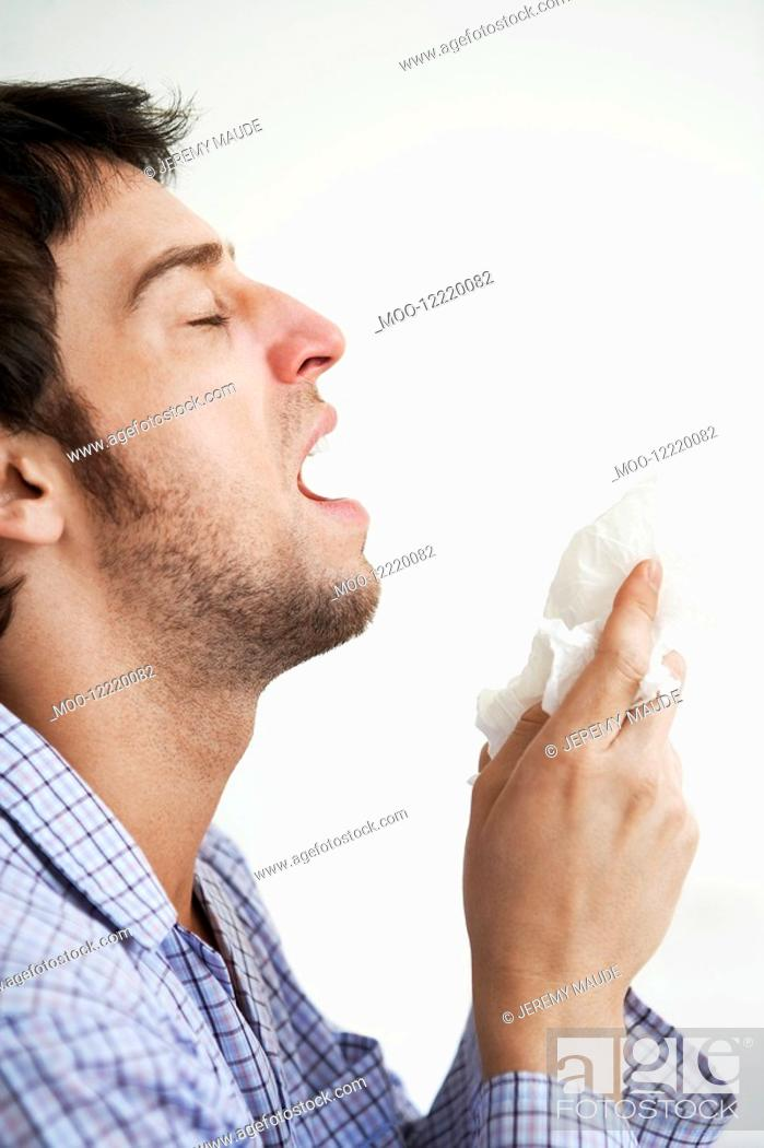 Stock Photo: Man about to sneeze into facial tissue.