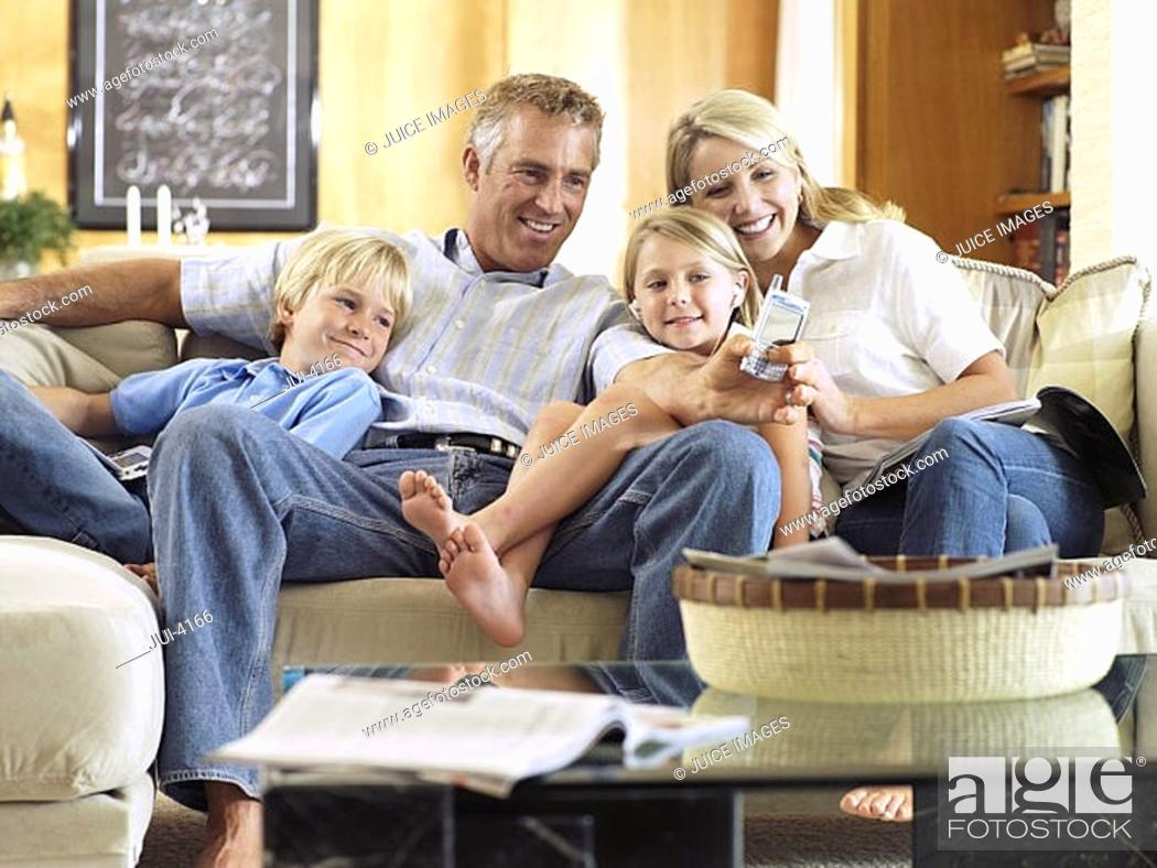 Stock Photo: Two generation family sitting on sofa at home, man taking photograph with camera phone, smiling.