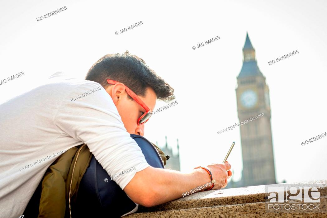 Stock Photo: Young man outdoors, leaning on wall, looking at smartphone, Big Ben in background, London, England, UK.