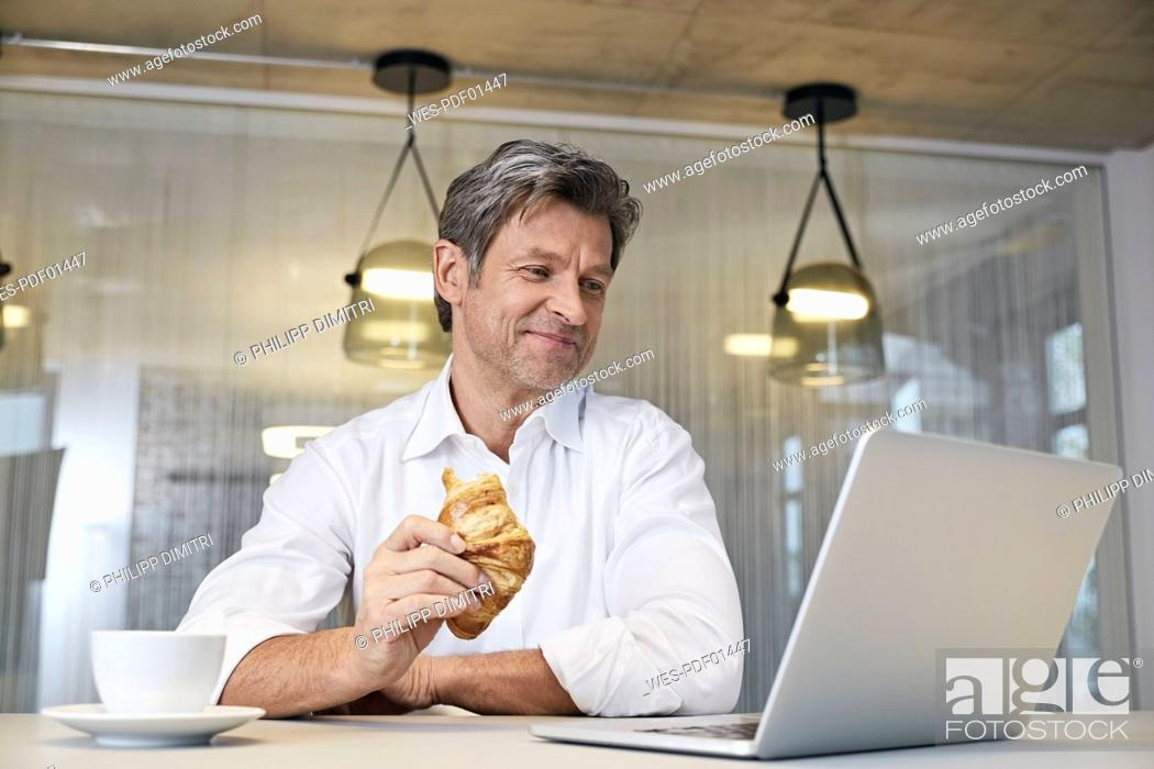 Stock Photo: Businessman using laptop while eating croissant.