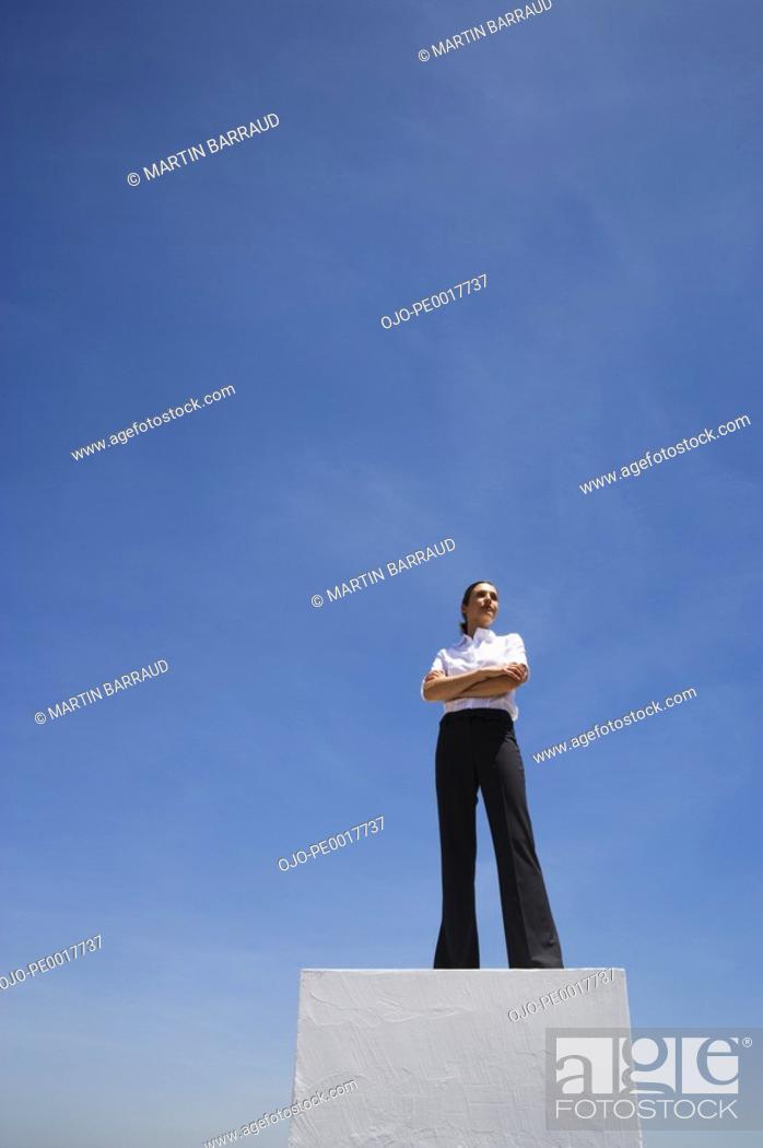 Stock Photo: Businesswoman standing on pedestal outdoors.