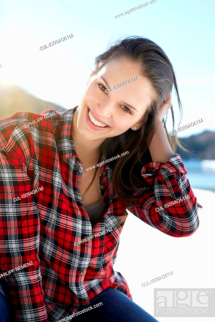 Photo de stock: Portrait of young woman with hand in hair at snow covered lakeside, German Alps, Germany.
