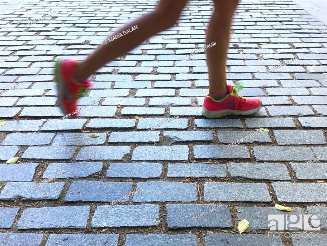 Stock Photo: Runner's legs running on pavement.