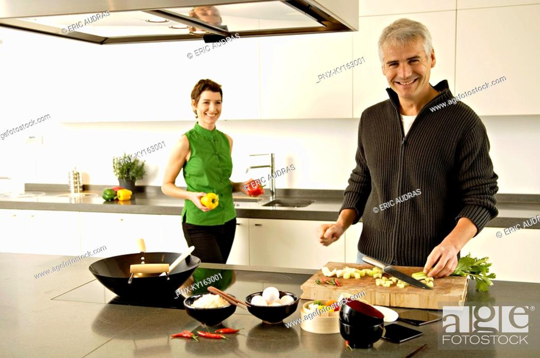 Stock Photo: Portrait of a mature man and a mid adult woman preparing food in the kitchen.
