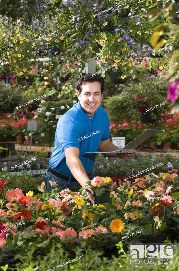 Stock Photo: Florist taking inventory in nursery.