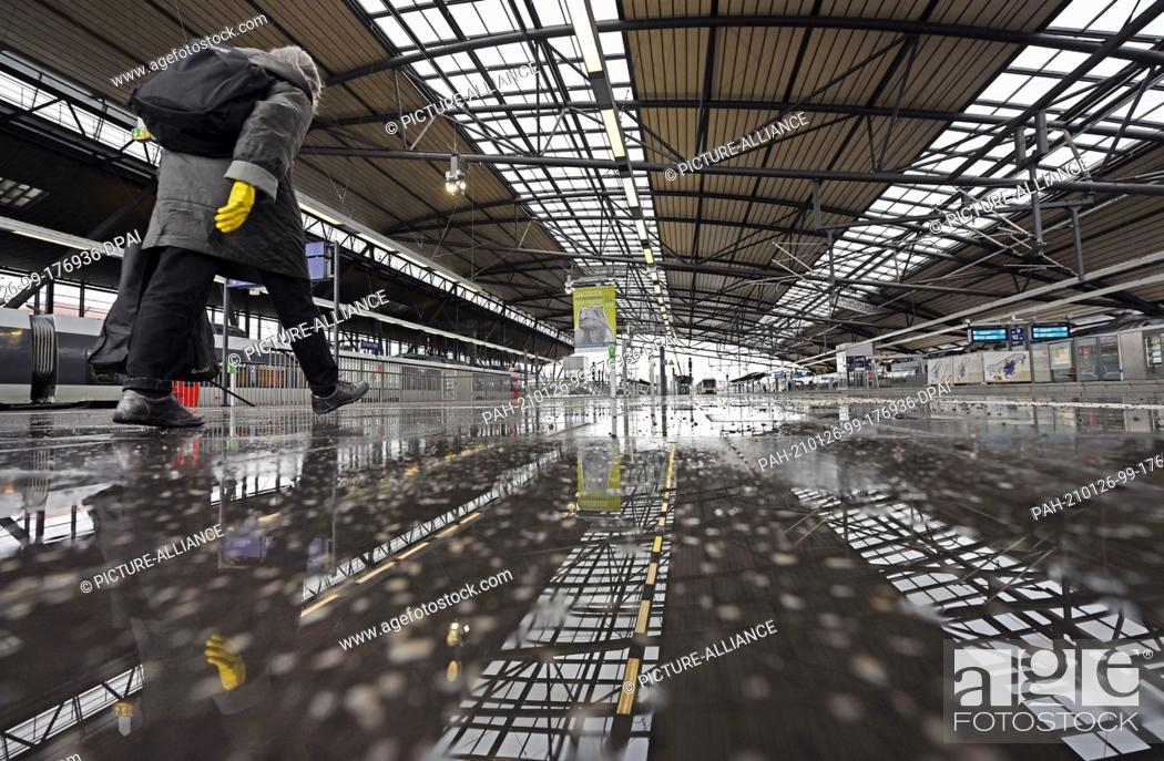 Imagen: 26 January 2021, Thuringia, Erfurt: A woman walks across the otherwise deserted platforms of the main station. The number of new coronavirus infections detected.