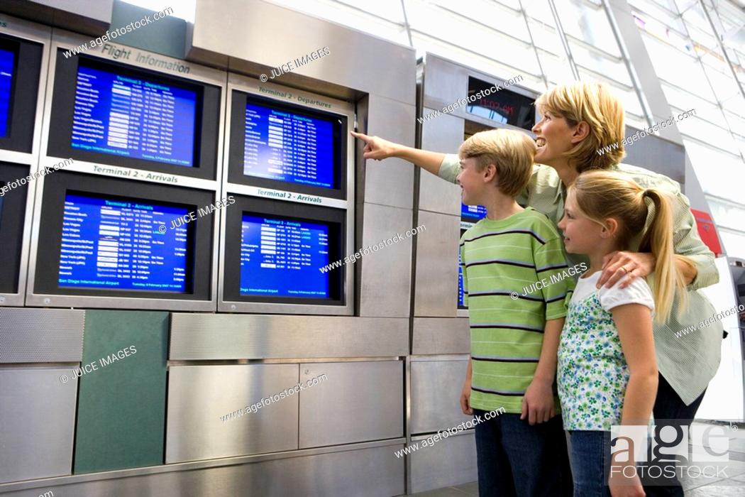 Stock Photo: Mother and children looking at flight information screen in airport departure lounge, woman pointing, smiling.