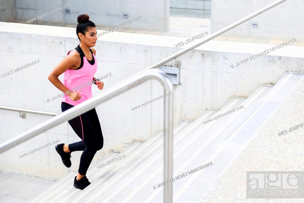 Stock Photo: Young woman running up stairs.