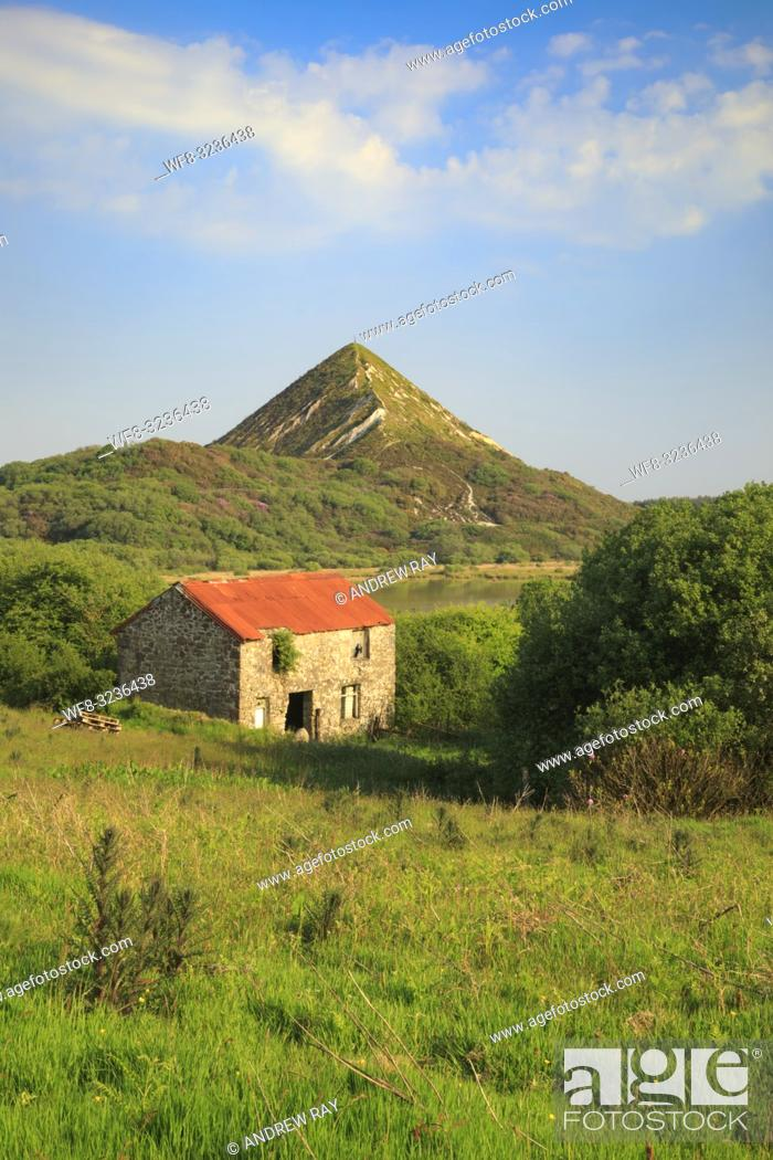 Stock Photo: Great Treverbyn China Clay Tip near St Austell in Cornwall with a disused barn providing foreground interest. The image was captured on an evening in late May.