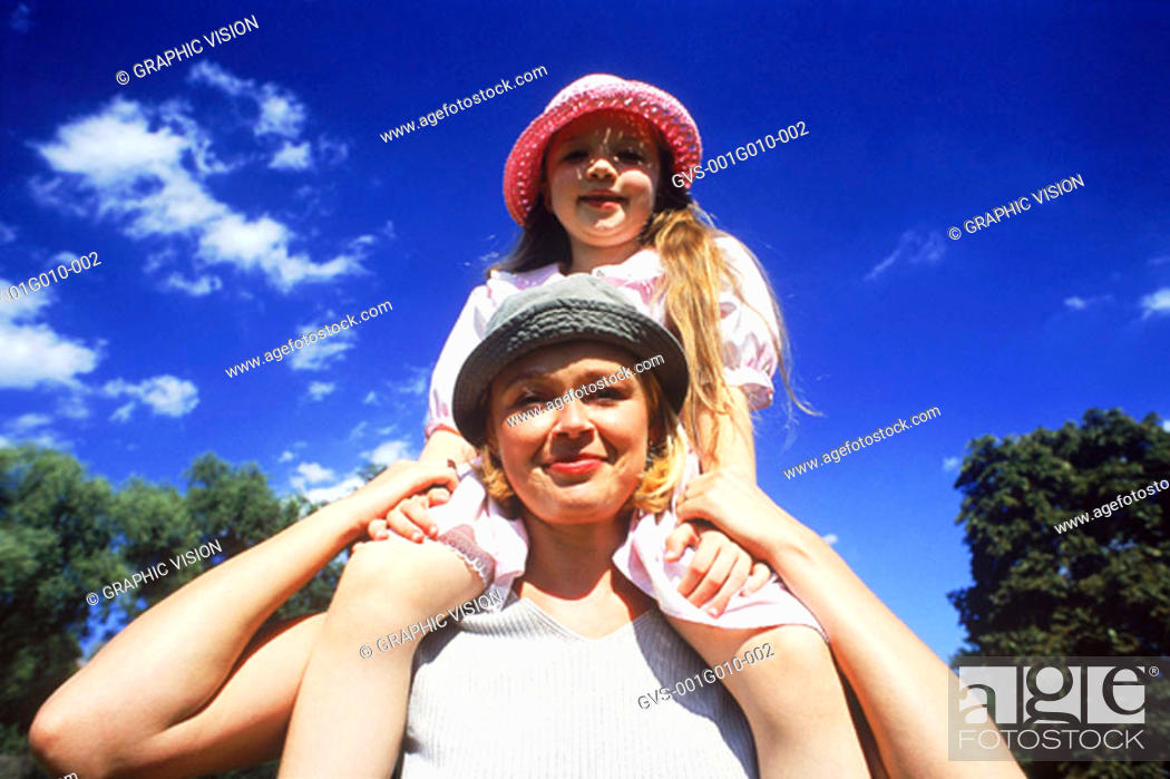 Stock Photo: Portrait of mother carrying daughter on shoulders.