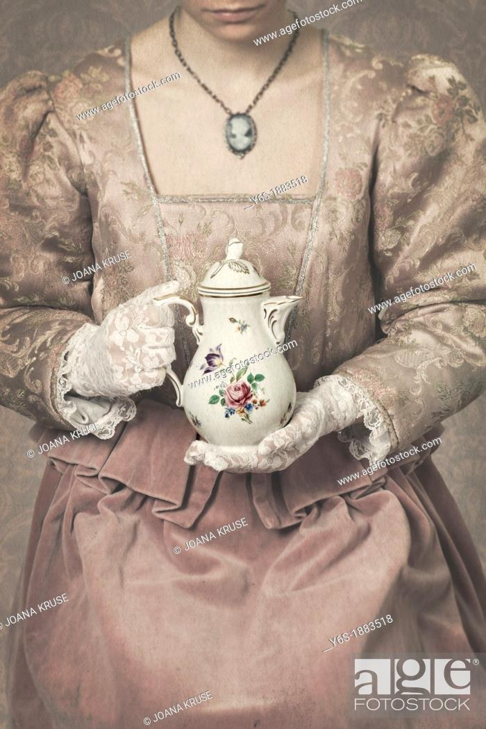 Stock Photo: a woman in a period dress is holding a coffee pot.