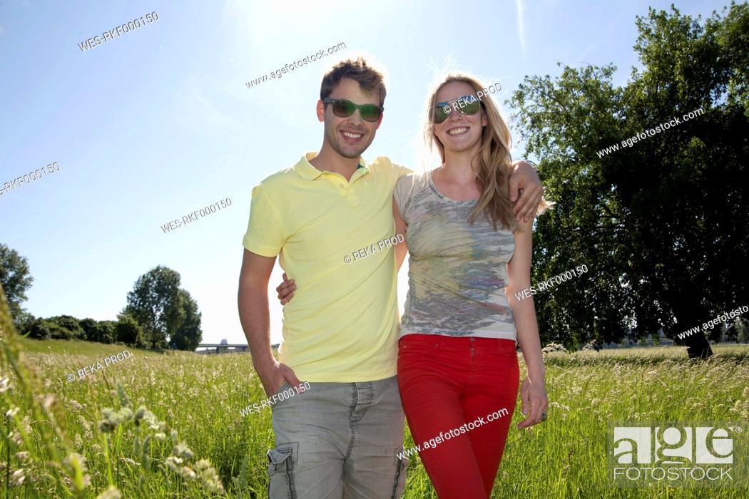 Stock Photo: Germany, North Rhine Westphalia, Duesseldorf, Couple walking in grass, smiling.