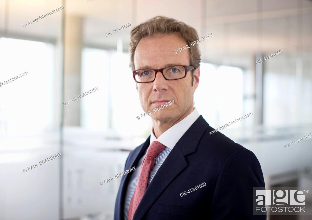Stock Photo: Businessman standing in office hallway.