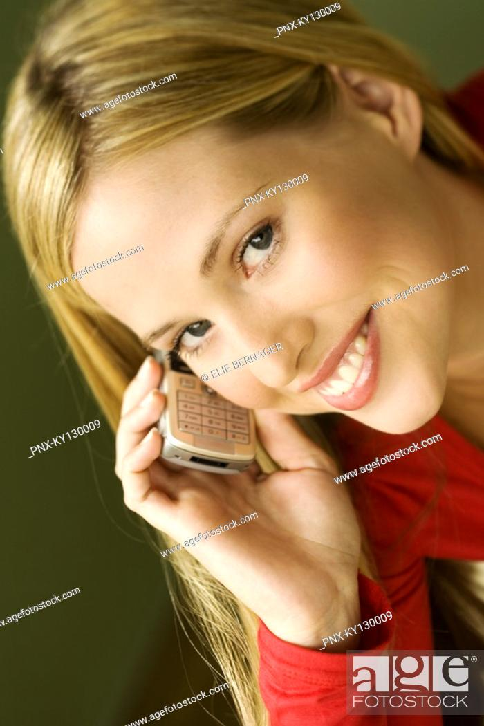 Stock Photo: Portrait of a young smiling woman, using mobile phone.