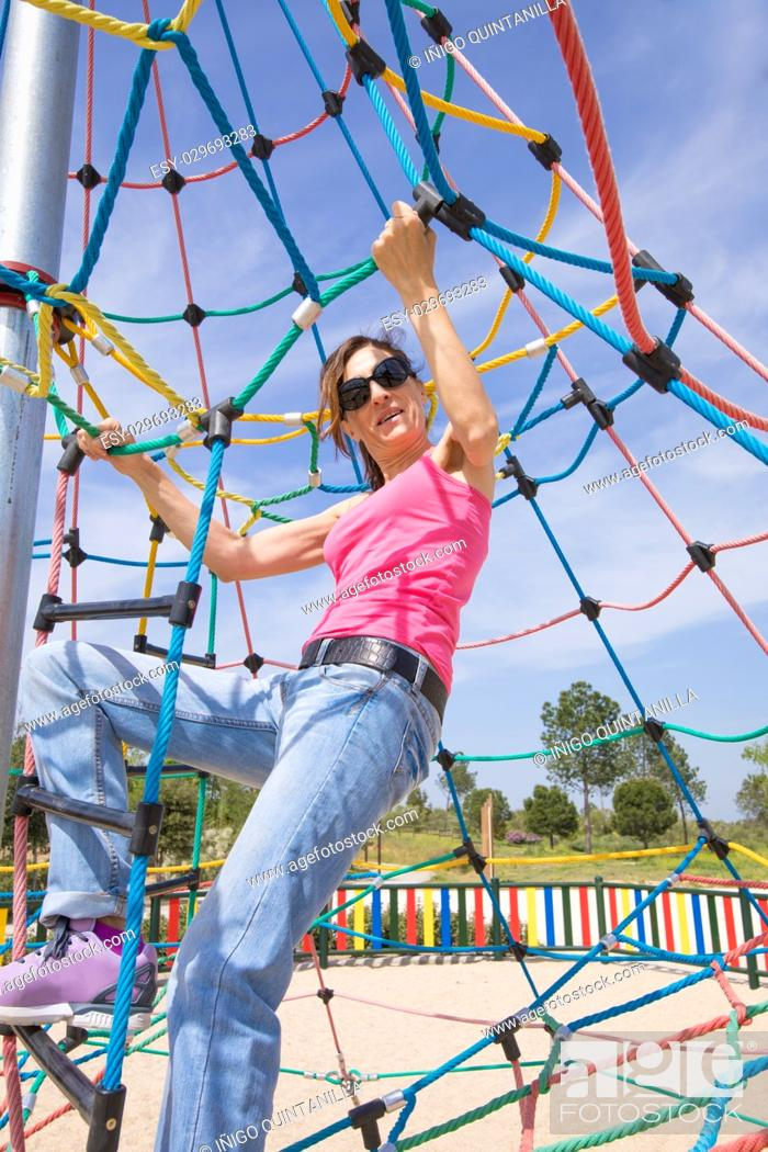 Stock Photo: adult woman dressed in pink shirt, blue jeans and sunglasses in outdoor playground climbing rode ladder.