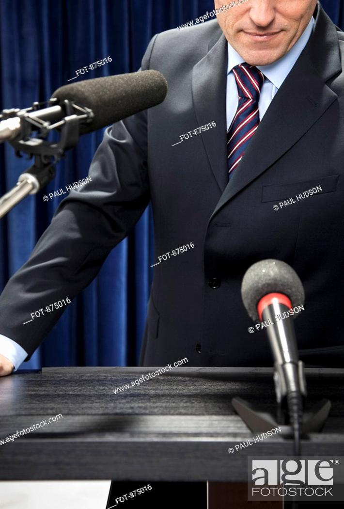 Imagen: Detail of a man standing at a lectern.