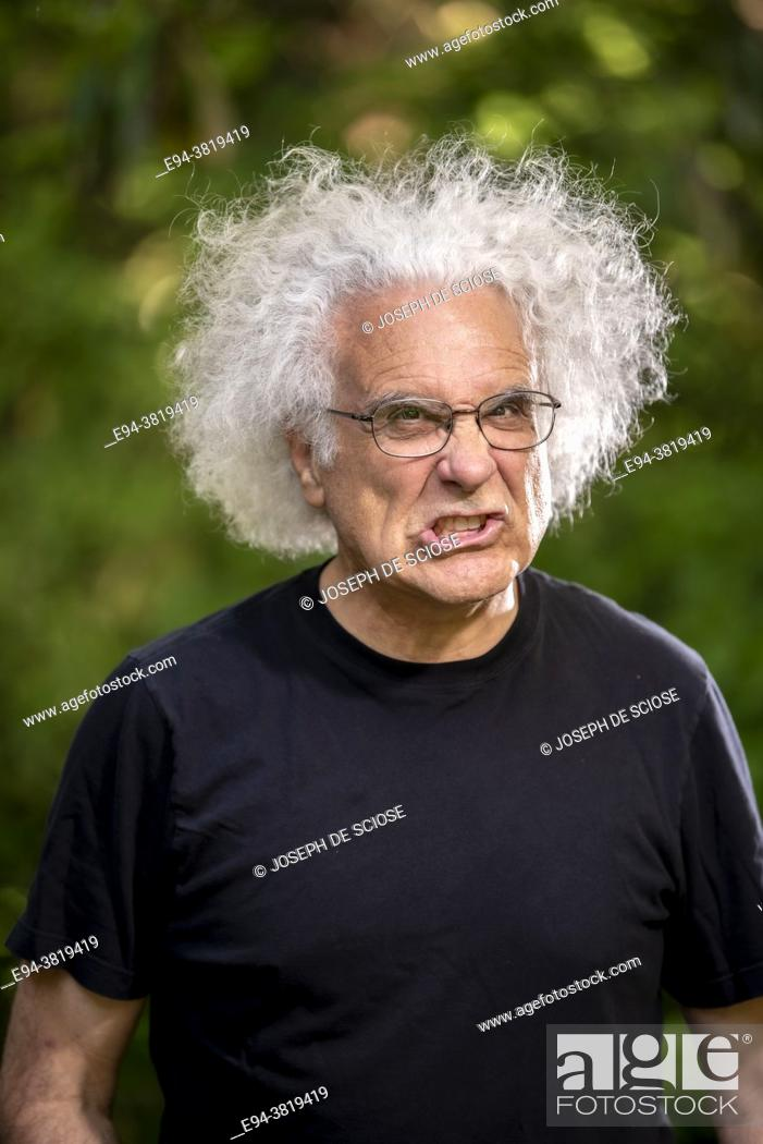 Stock Photo: A grey haired 68 year old man making a face at the camera.