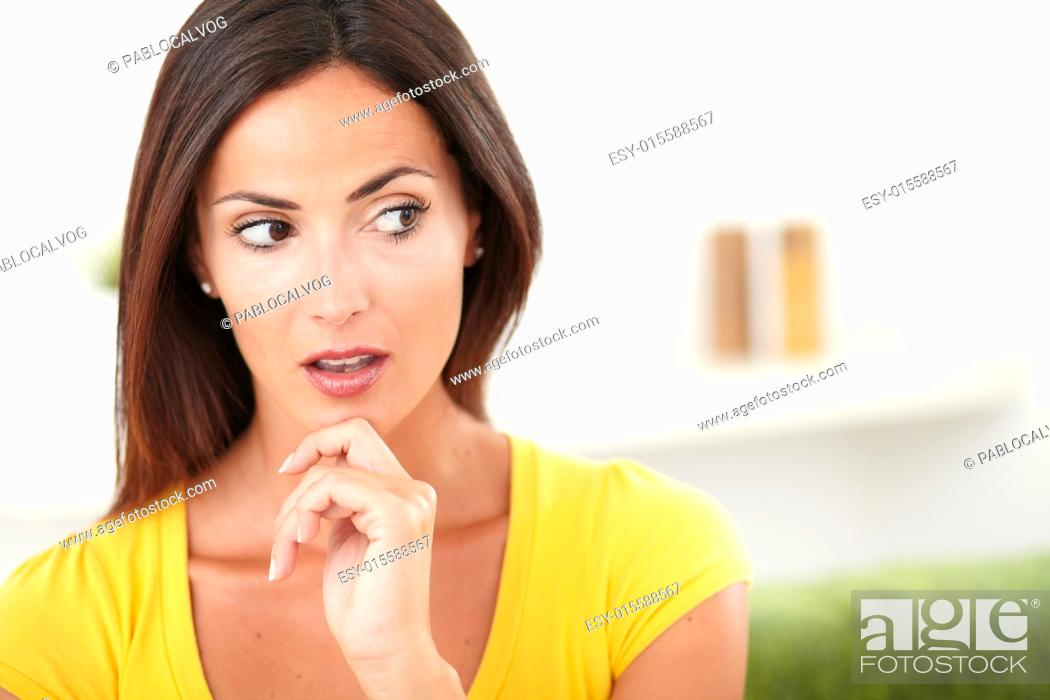 Stock Photo: Surprised woman looking away while contemplating with one hand on her chin - copy space.