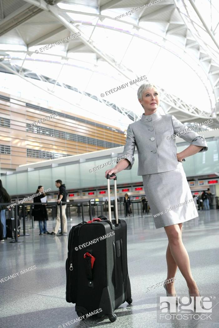 Stock Photo: Mature woman standing in airport with luggage.