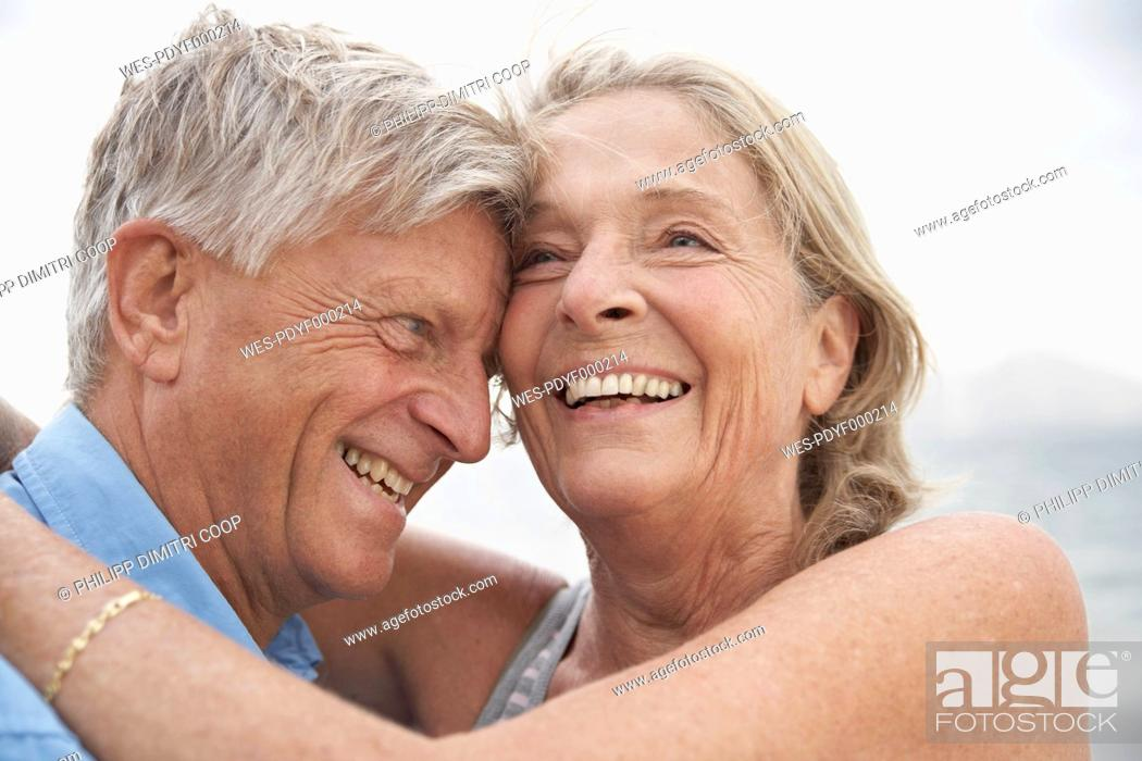 Stock Photo: Spain, Mallorca, Senior couple embracing on beach.