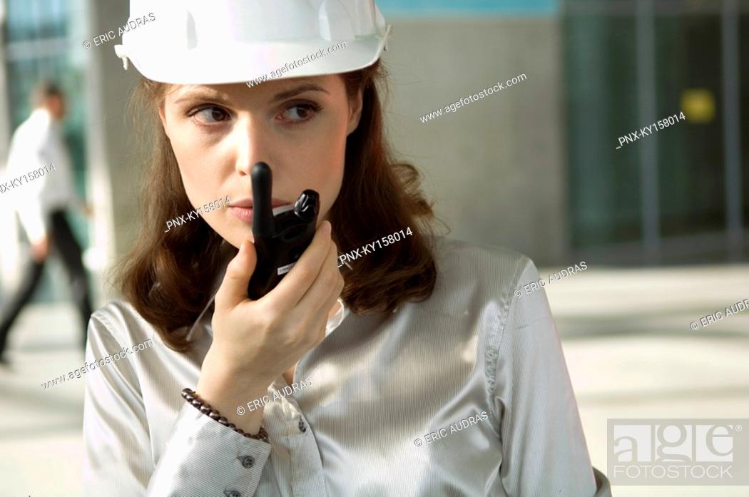 Stock Photo: Close-up of a young woman talking on a walkie-talkie.