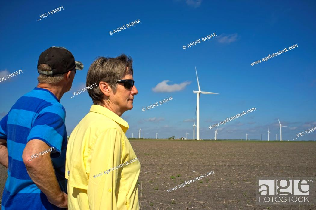 Stock Photo: Man and woman looking at a field of wind turbine energy generators.