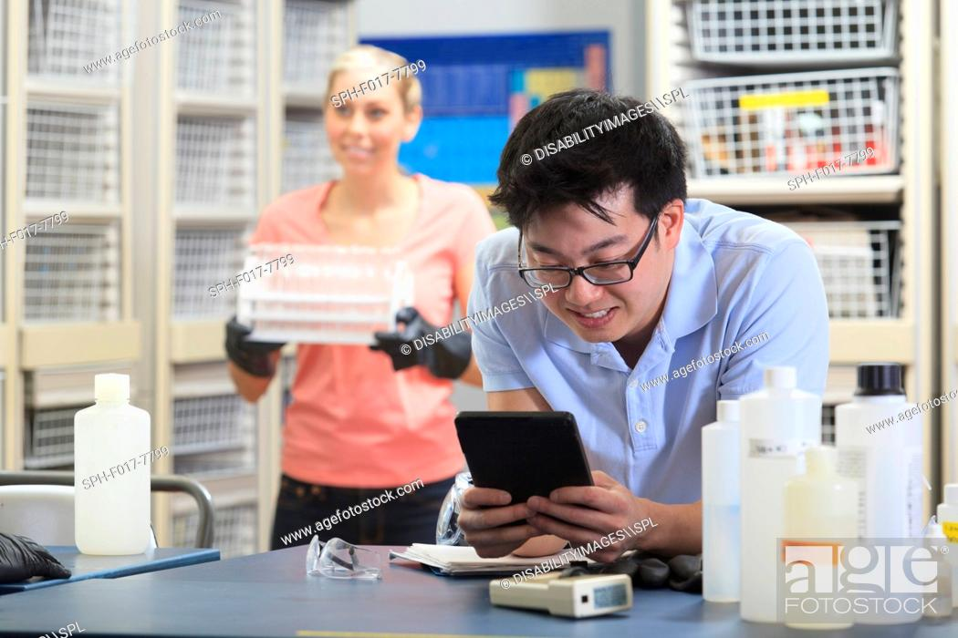 Stock Photo: Engineering student using a tablet to record data in chemistry laboratory.