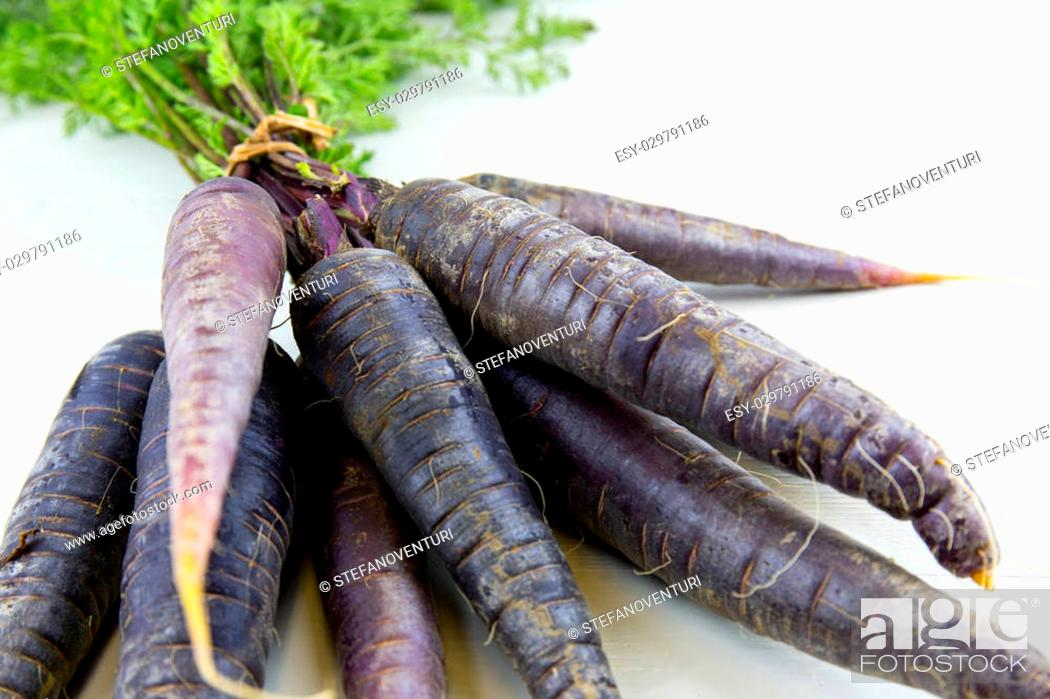 Photo de stock: Bunch of heirloom purple carrots, over white and wooden background.