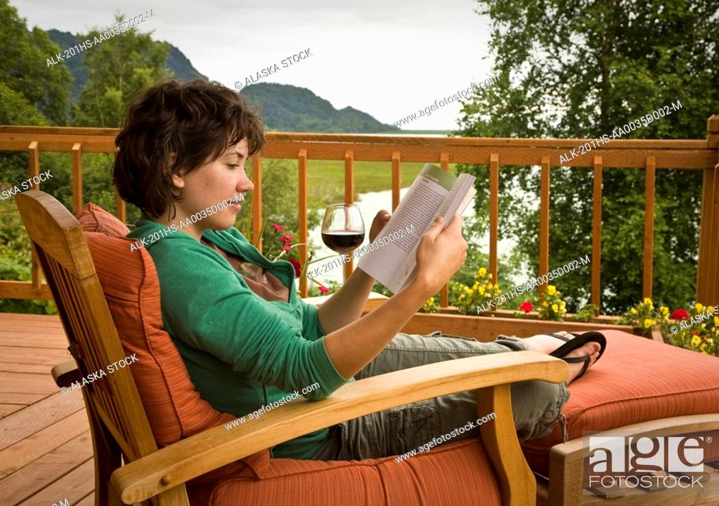 Stock Photo: Guest reads & relaxes in a deck chair at Redoubt Bay Lodge in the Big River Lakes area. Redoubt Bay State Critical Habitat Area, Southcentral, Alaska.