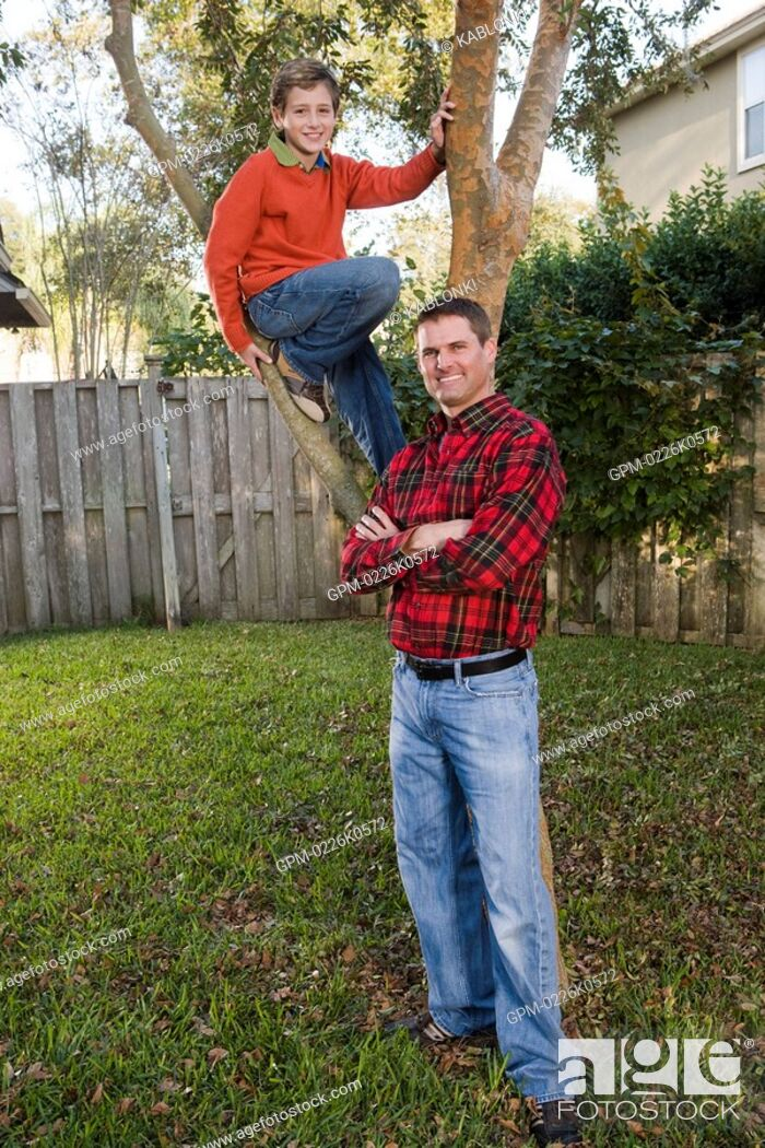 Imagen: Portrait of happy father and son posing beside tree in backyard, looking at camera.