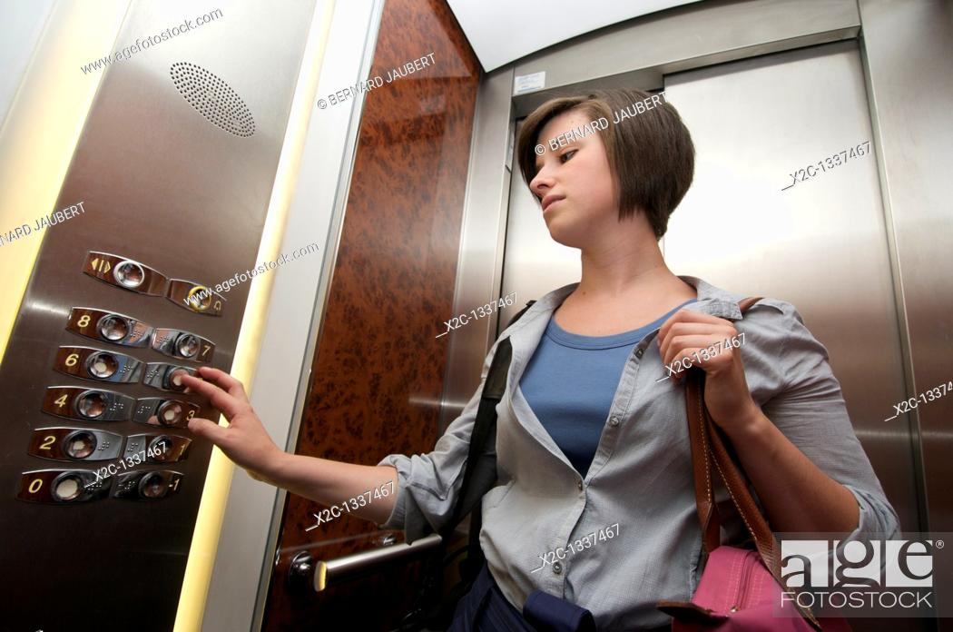 Stock Photo: Young woman pressing on a button in an elevator.
