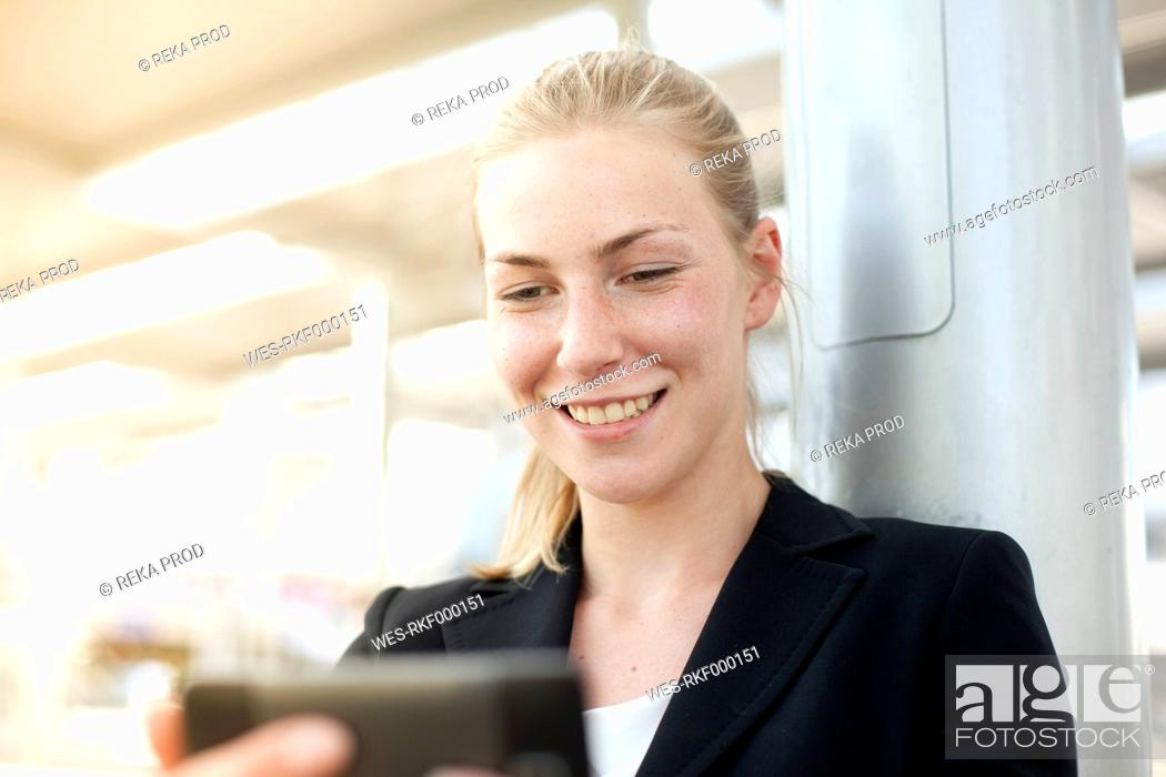 Stock Photo: Germany, North Rhine Westphalia, Duesseldorf, Young woman using smart phone at station.