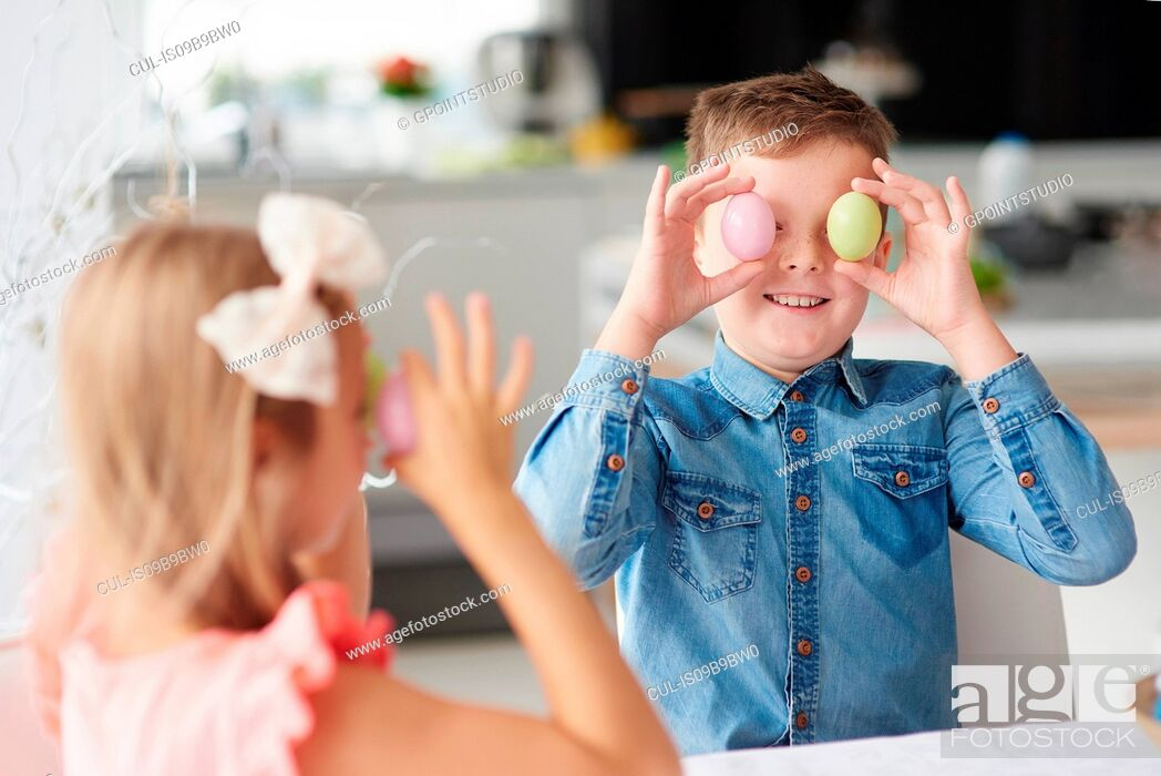 Photo de stock: Girl with brother holding easter eggs over their eyes.