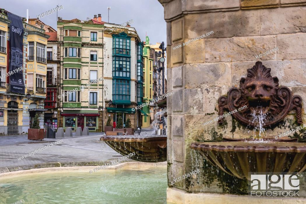 Stock Photo: Tenement houses and fountain of Statue of Pelagius, first king of Asturias in Gijon in the autonomous community of Asturias in Spain.