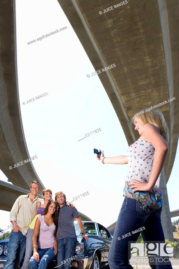 Stock Photo: Young woman taking photograph of friends on bonnet of car beneath overpass, low angle view.