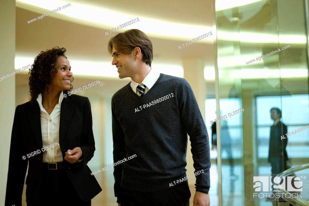 Stock Photo: Executives talking as they walk together in corridor.