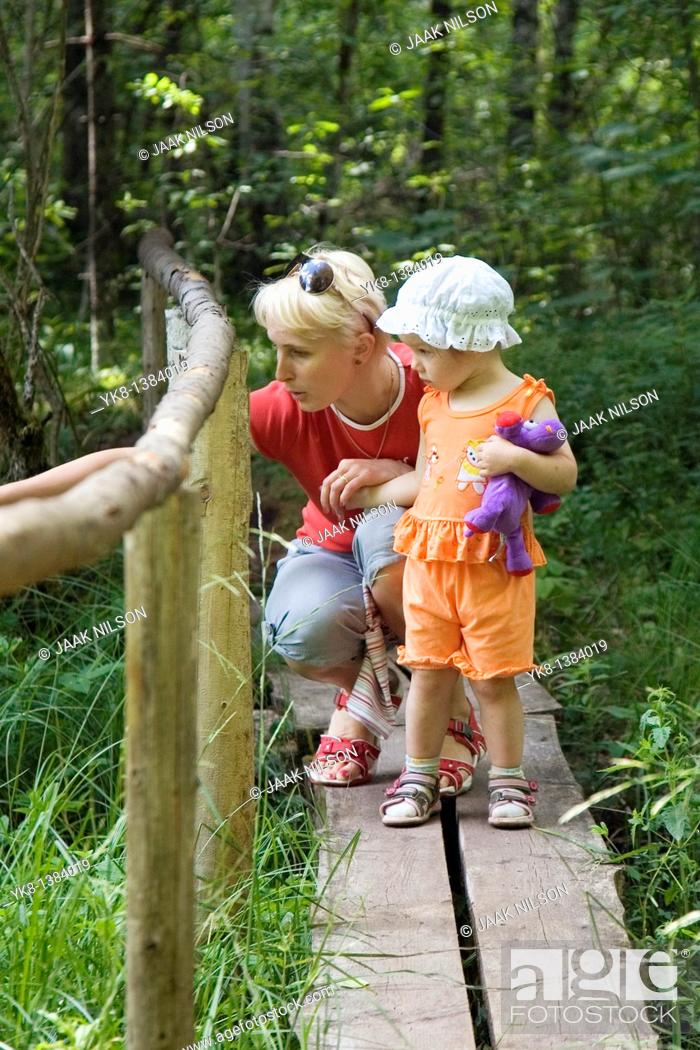Stock Photo: Mother with Kid Girl Standing on Wooden Boardwalk with Fence in Forest.