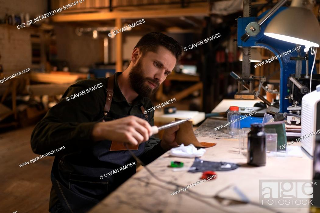 Imagen: Focused craftsman using pyrography machine on leather.
