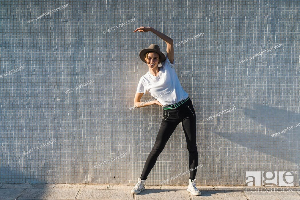 Stock Photo: Smiling woman wearing hat standing in front of tiled wall doing stretching exercises.