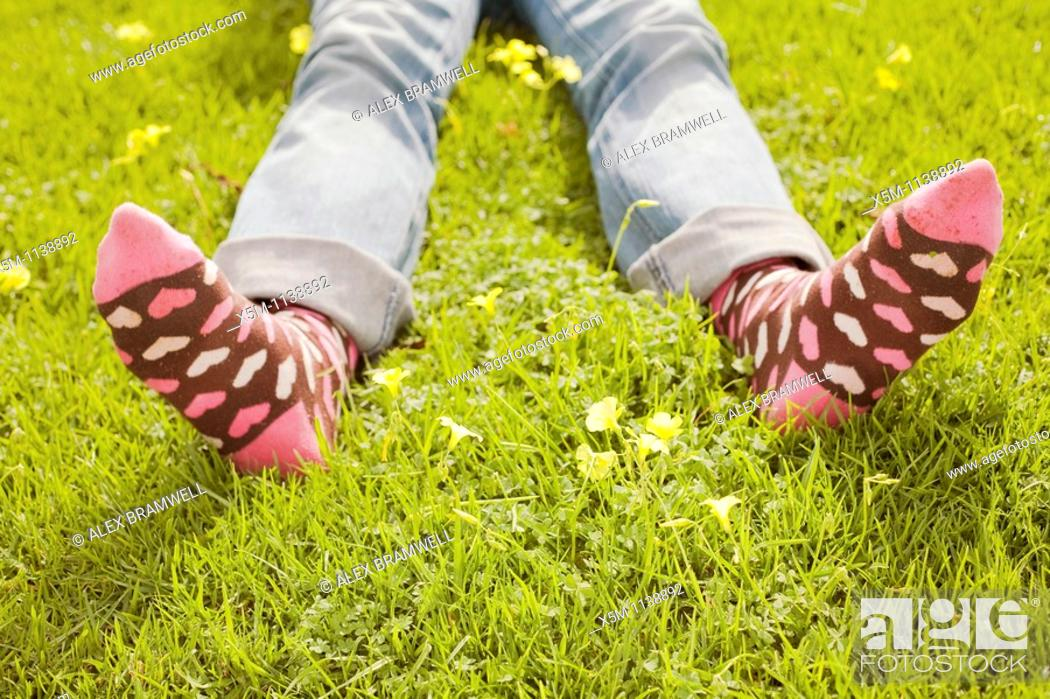 Stock Photo: Woman on a green lawn with decorative socks.