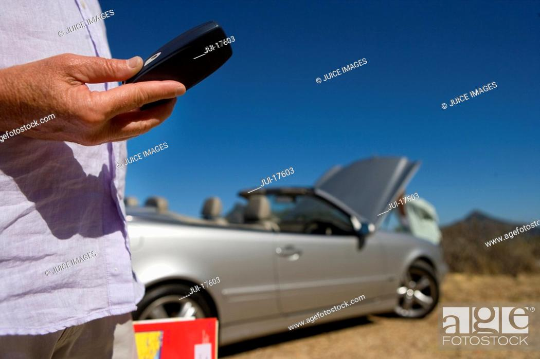 Stock Photo: Man calling for roadside assistance.